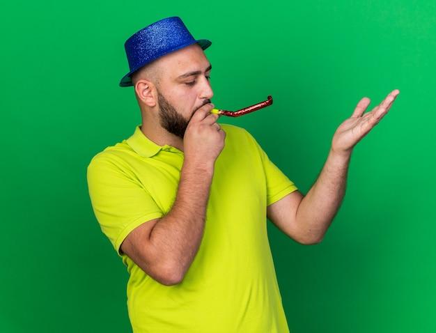 Tevreden jonge man met een blauwe feestmuts die een feestfluitje blaast en zijn hand opsteekt, geïsoleerd op een groene muur