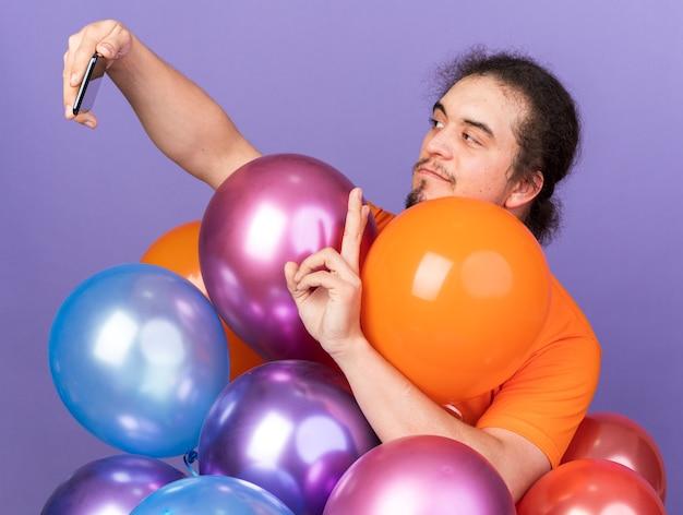 Tevreden jonge man met een oranje t-shirt die achter ballonnen staat en een selfie maakt met vredesgebaar geïsoleerd op een paarse muur