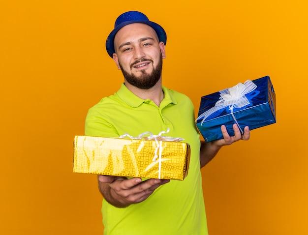 Tevreden jonge man met feestmuts die geschenkdozen naar de camera steekt