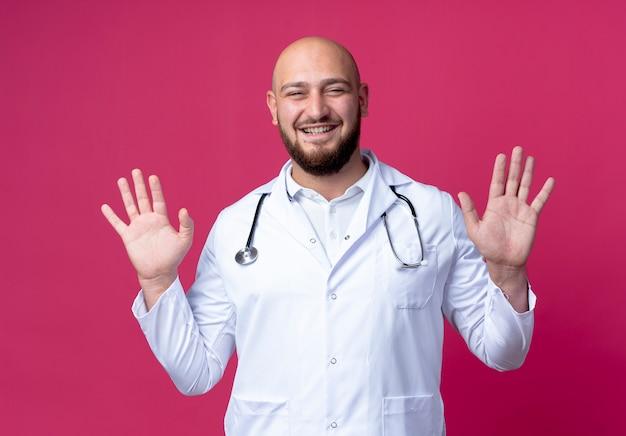 Tevreden jonge mannelijke arts die medische mantel en stethoscoop hand in hand draagt