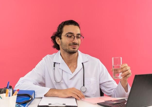 Tevreden jonge mannelijke arts met een medische bril die een medische mantel draagt met een stethoscoop die aan het bureau zit