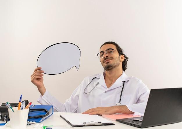 Tevreden jonge mannelijke arts met medische bril die medische mantel met een stethoscoop draagt