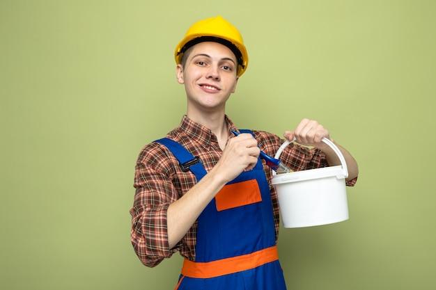 Tevreden jonge mannelijke bouwer die een uniforme emmer met verfborstel draagt