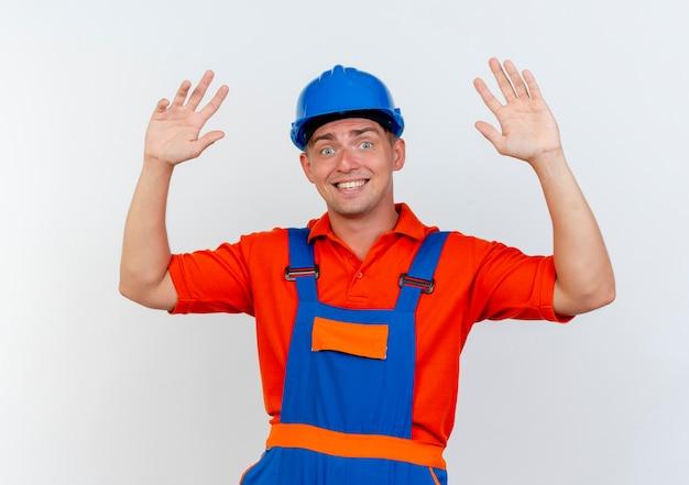 Tevreden jonge mannelijke bouwer die eenvormig en veiligheidshelm draagt die handen op wit opheffen