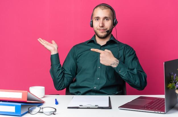 Tevreden jonge mannelijke callcenter-operator die een headset draagt die aan het bureau zit met kantoorhulpmiddelen die doen alsof hij vasthoudt en naar iets wijst