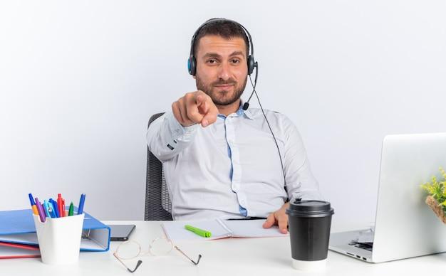 Tevreden jonge mannelijke callcentermedewerker met een headset die aan tafel zit met kantoorhulpmiddelen die je een gebaar laten zien dat op een witte muur wordt geïsoleerd