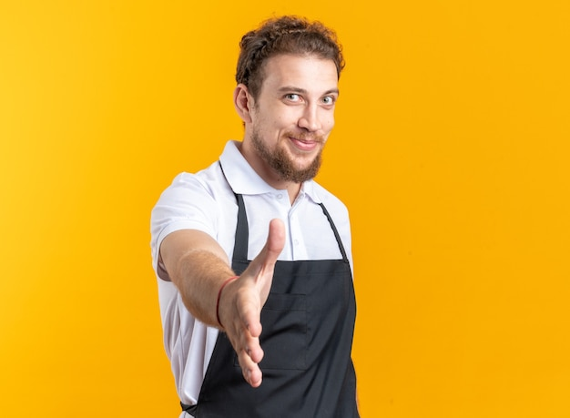 Tevreden jonge mannelijke kapper in uniform die hand uitsteekt naar camera geïsoleerd op gele muur