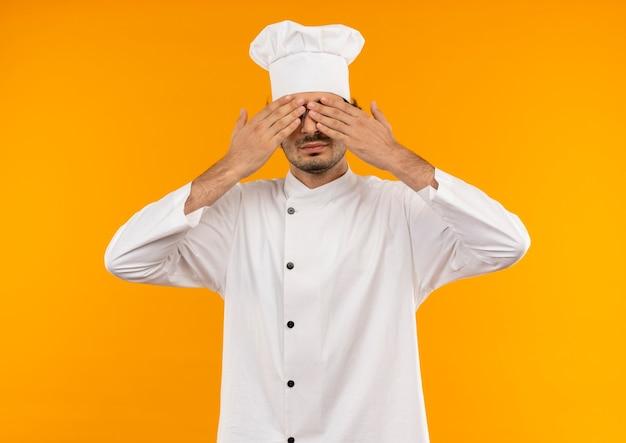 Tevreden jonge mannelijke kok die eenvormige chef-kok draagt en glazen bedekken ogen met handen die op gele muur worden geïsoleerd