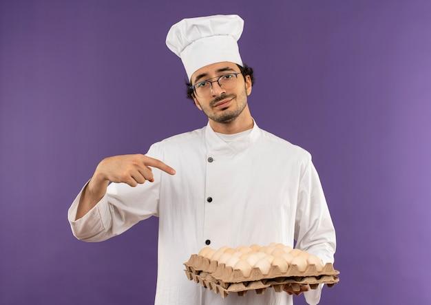 Tevreden jonge mannelijke kok die eenvormige chef-kok en glazen bedrijf draagt en wijst naar partij eieren op paars