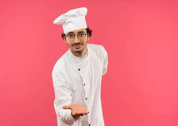 Tevreden jonge mannelijke kok die eenvormige chef-kok en glazen draagt die hand standhoudt die op roze muur wordt geïsoleerd