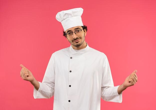 Tevreden jonge mannelijke kok die eenvormige chef-kok en glazen draagt die ja gebaren toont die op roze muur worden geïsoleerd