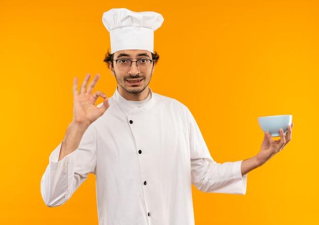 Tevreden jonge mannelijke kok die eenvormige chef-kok en glazen draagt die kom houdt en okeygebaar toont dat op gele muur wordt geïsoleerd