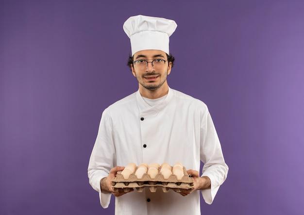 Tevreden jonge mannelijke kok die eenvormige chef-kok en glazen draagt die partij eieren op paars houdt