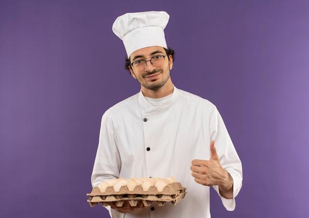 Tevreden jonge mannelijke kok die eenvormige chef-kok en glazen draagt die partij eieren zijn duim tegen paars houdt