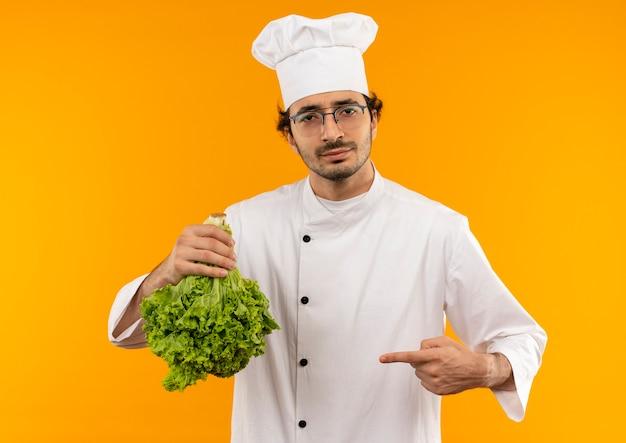 Tevreden jonge mannelijke kok die eenvormige chef-kok en glazenholding draagt en wijst naar salade die op gele muur wordt geïsoleerd