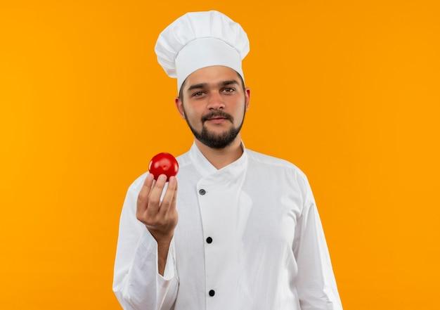 Tevreden jonge mannelijke kok die in tomaat van de chef-kok eenvormige holding geïsoleerd op oranje ruimte kijken