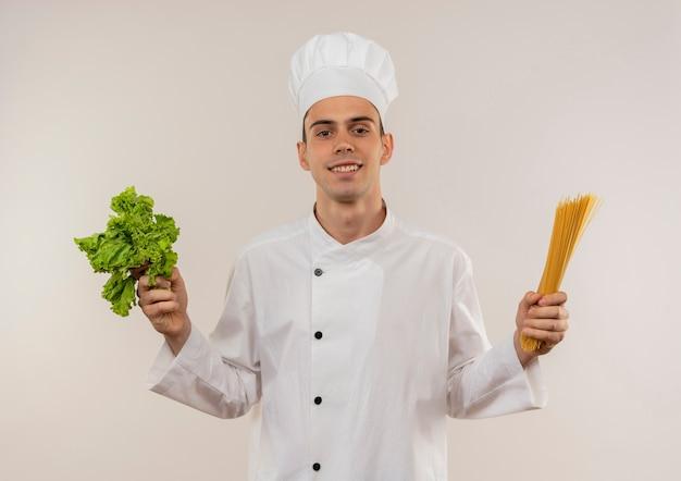 Tevreden jonge mannelijke kok die spaghetti en salade van de chef-kok de eenvormige holding draagt