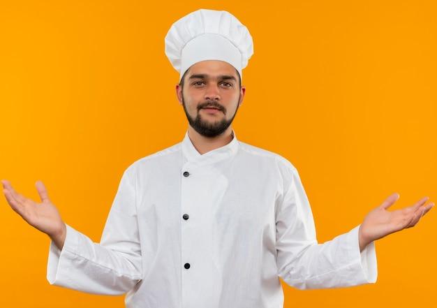 Tevreden jonge mannelijke kok in eenvormige chef-kok die lege handen toont en geïsoleerd op oranje ruimte kijkt