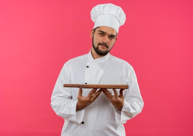 Tevreden jonge mannelijke kok in snijplank van de chef-kok de eenvormige die op roze ruimte wordt geïsoleerd