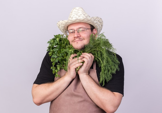 Tevreden jonge mannelijke tuinman die tuinieren hoed draagt die dille met koriander rond gezicht houdt dat op witte muur wordt geïsoleerd