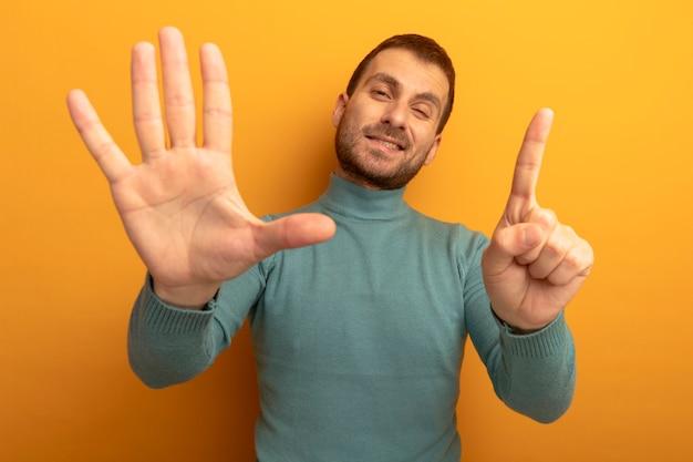Tevreden jonge mens die voorzijde bekijkt die met zes met handen knipogen toont die op oranje muur worden geïsoleerd