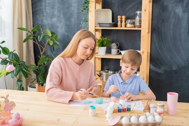Tevreden jonge moeder zittend aan een houten tafel en zoon helpen om eieren te schilderen voor het paasfeest
