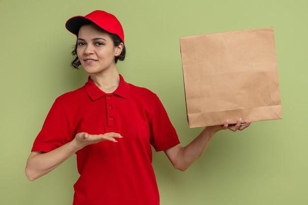 Tevreden jonge mooie bezorger die met de hand naar een papieren voedselzak wijst en vasthoudt