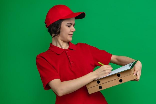 Tevreden jonge mooie bezorger die op het klembord schrijft en pizzadozen vasthoudt