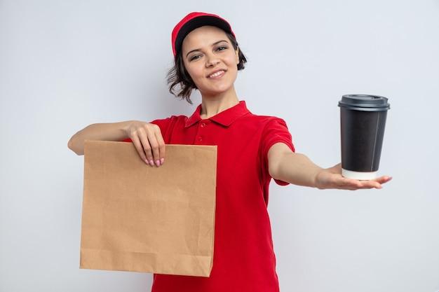 Tevreden jonge mooie bezorger die papieren voedselverpakkingen en afhaalbeker vasthoudt