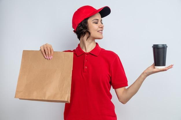 Tevreden jonge mooie bezorger die papieren voedselverpakkingen vasthoudt en naar een afhaalbeker kijkt