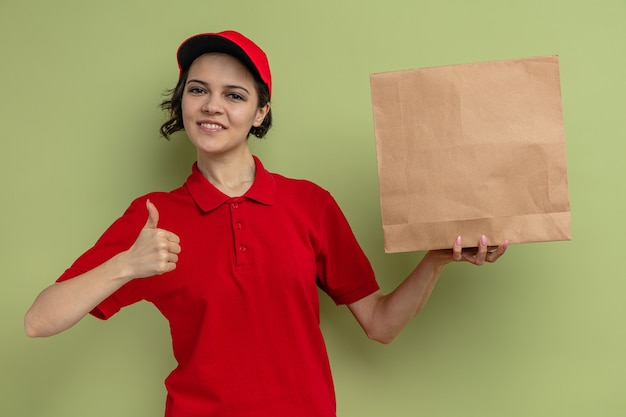 Tevreden jonge mooie bezorger die papieren voedselverpakkingen vasthoudt en omhoog steekt