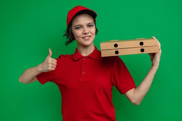 Tevreden jonge mooie bezorger die pizzadozen op haar schouder houdt en omhoog duimt