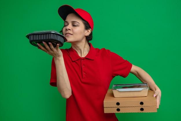 Tevreden jonge mooie bezorger die voedselverpakkingen op pizzadozen vasthoudt en voedselcontainer snuffelt