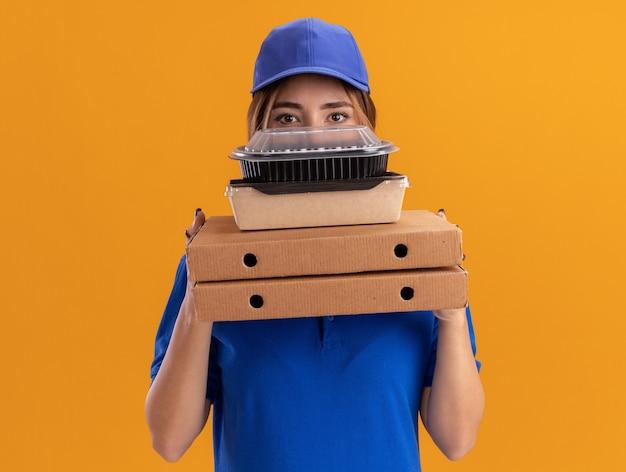 Tevreden jonge mooie bezorger in uniform houdt papieren voedselpakketten en containers op pizzadozen geïsoleerd op een oranje muur