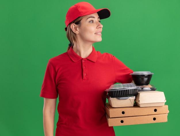 Tevreden jonge mooie bezorger in uniform houdt papieren voedselpakketten en containers op pizzadozen