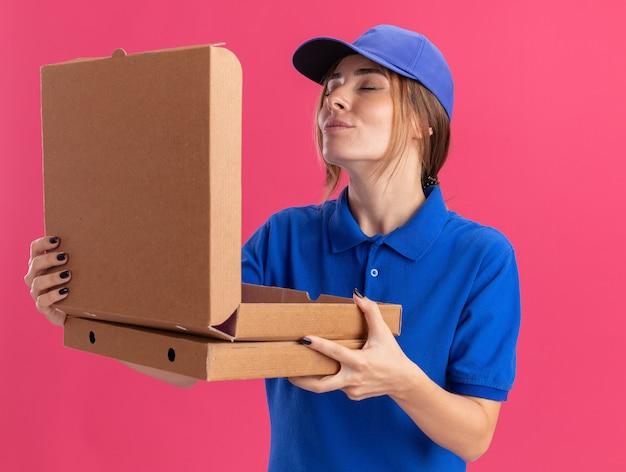 Tevreden jonge mooie bezorger in uniform houdt pizzadozen vast en doet alsof ze aan roze snuift