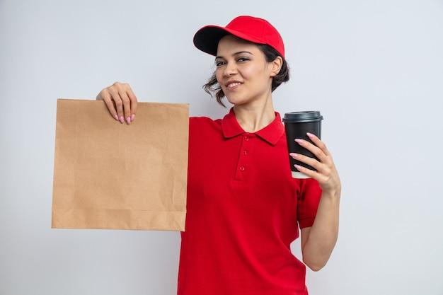 Tevreden jonge mooie bezorger met papieren voedselverpakking en afhaalbeker