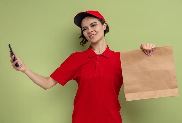 Tevreden jonge mooie bezorger met papieren voedselverpakking en telefoon