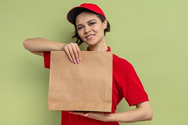 Tevreden jonge mooie bezorger met papieren voedselzak