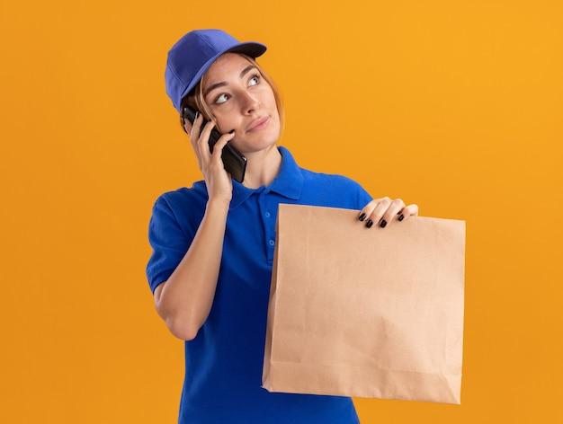 Tevreden jonge mooie bezorgvrouw in uniform houdt papieren pakket en praat over de telefoon kijken naar kant geïsoleerd op oranje muur