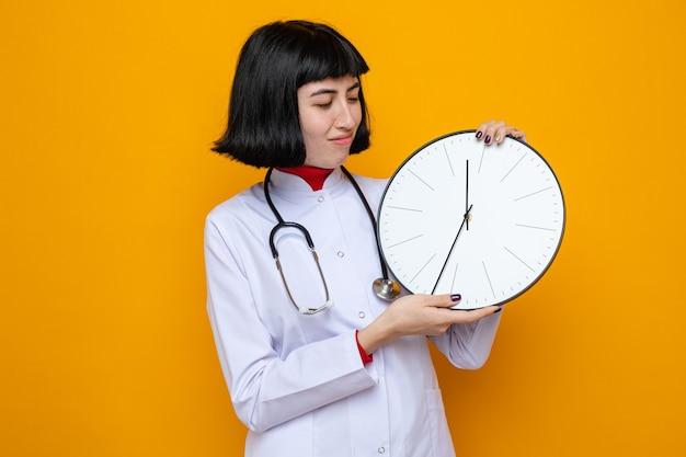 Tevreden jonge, mooie blanke vrouw in doktersuniform met een stethoscoop die de klok vasthoudt en bekijkt