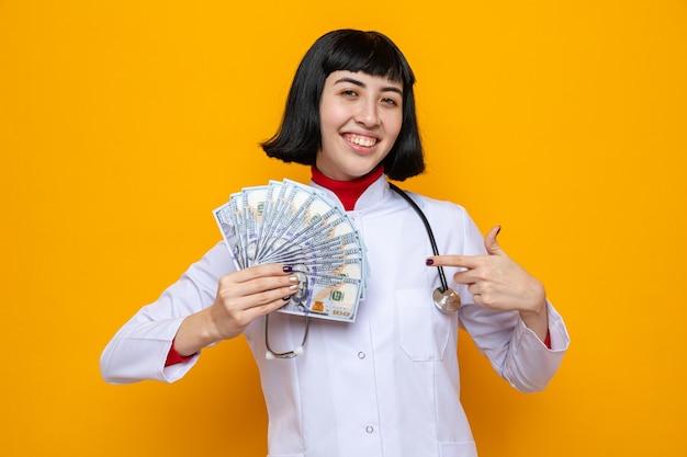 Tevreden jonge, mooie blanke vrouw in doktersuniform met een stethoscoop die vasthoudt en naar geld wijst