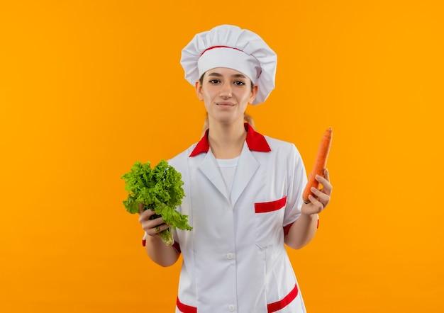 Tevreden jonge mooie kok in de sla en de wortel van de chef-kok de eenvormige die op oranje ruimte wordt geïsoleerd