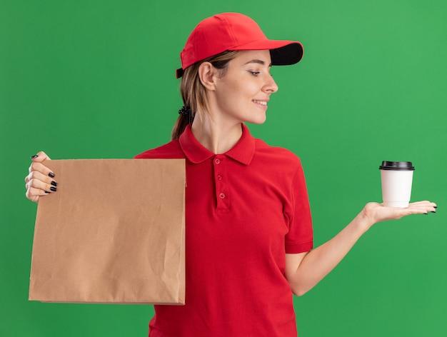Tevreden jonge mooie levering meisje in uniform houdt papieren pakket en kijkt naar papieren beker op groen