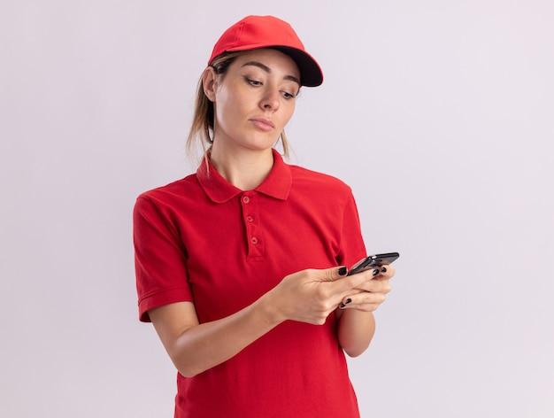 Tevreden jonge mooie leveringsvrouw in uniform houdt en kijkt naar telefoon die op witte muur wordt geïsoleerd