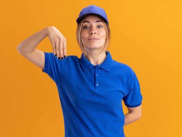 Tevreden jonge mooie leveringsvrouw in uniforme punten naar beneden met hand die op oranje muur wordt geïsoleerd