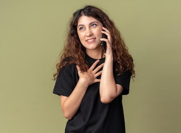 Tevreden jonge mooie vrouw die aan de telefoon praat terwijl ze opkijkt en een bedankgebaar doet geïsoleerd op een olijfgroene muur met kopieerruimte