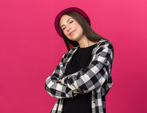 Tevreden jonge mooie vrouw die hoed draagt die handen kruist