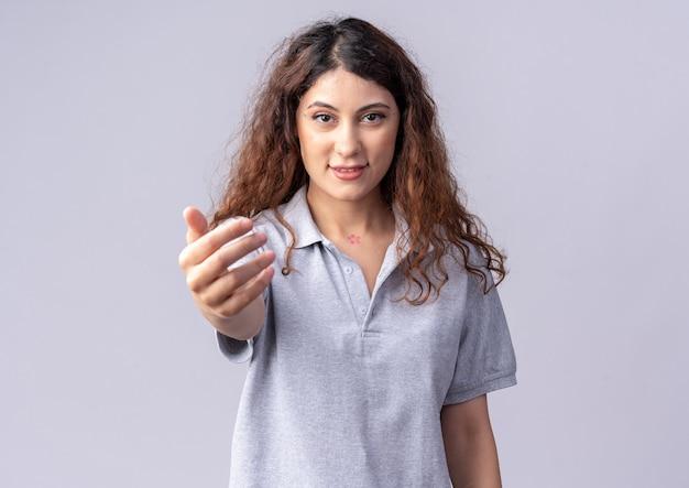 Tevreden jonge mooie vrouw die naar de voorkant kijkt en de hand uitstrekt naar de voorkant geïsoleerd op een witte muur met kopieerruimte