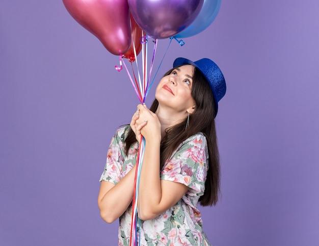 Tevreden jonge mooie vrouw met een feestmuts die ballonnen vasthoudt en bekijkt die op een blauwe muur zijn geïsoleerd
